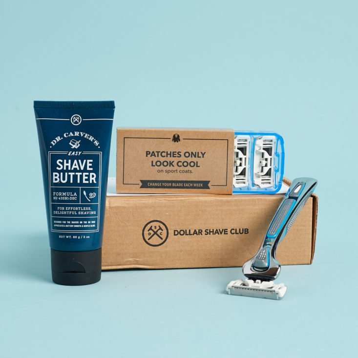 Dollar Shave Club starter kit with handle, shave butter, and pack of cartridges on blue backgound