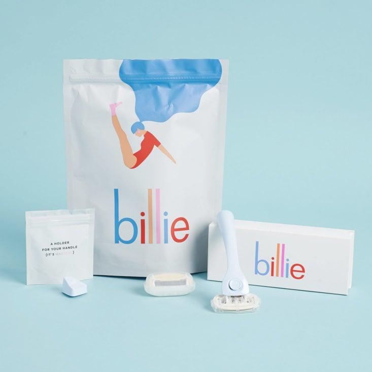 Billie Razor Starter Kit including bluue handle, 2 cartridges, and magnetic holder arranged around shipping bag.