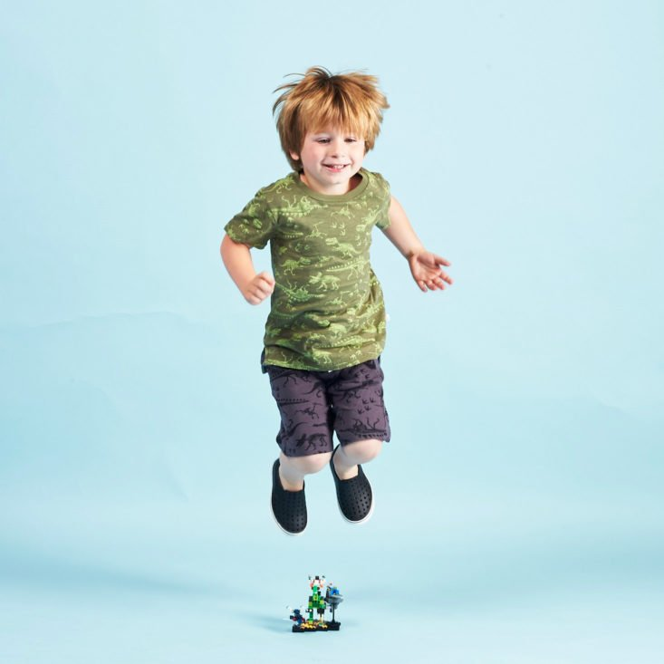 Stitch Fix Kids little boy wearing dinosaur print clothes, jumping over a toy.