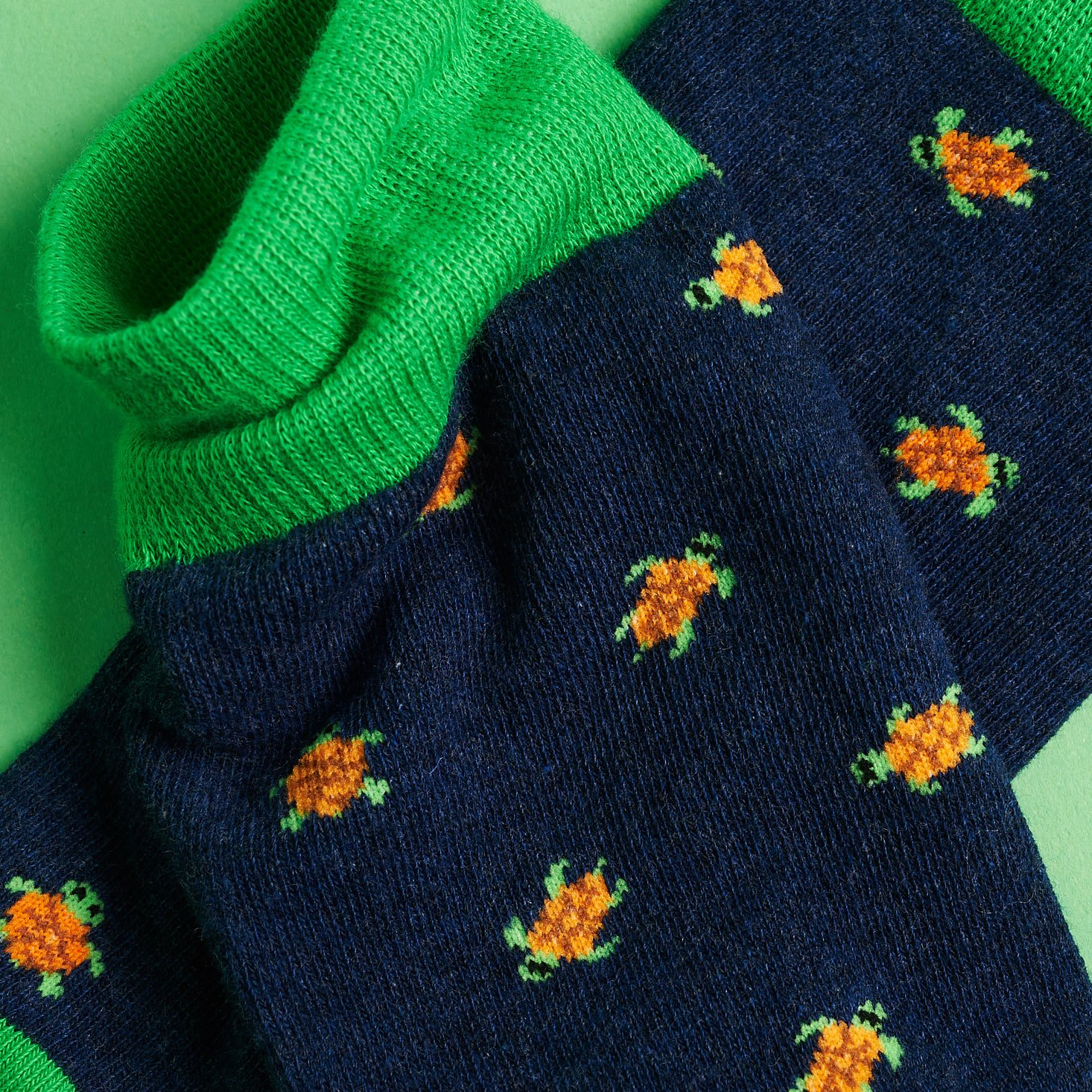 close up on the turtle designs and green cuffs of the socks