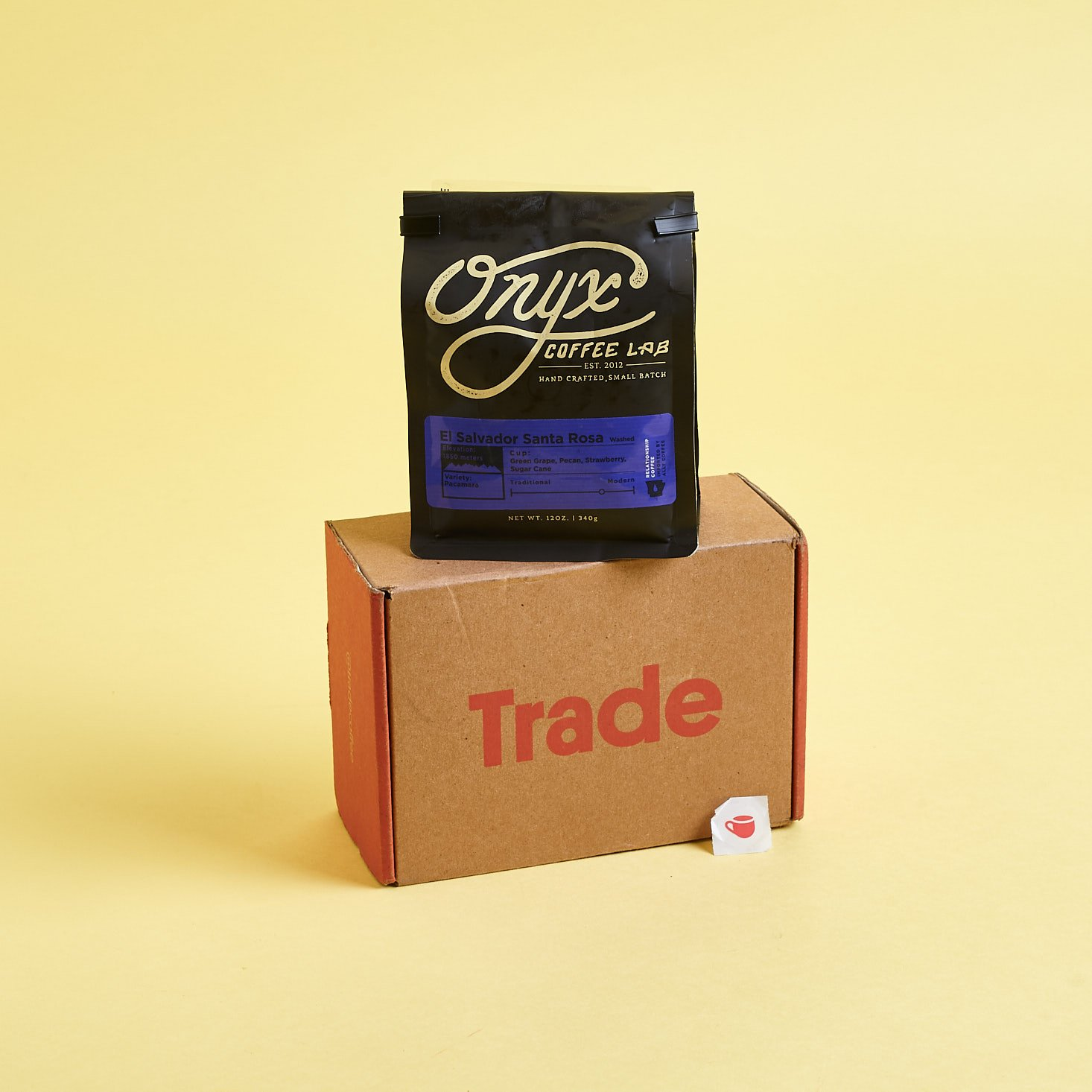 Trade Coffee box shown with a bag of whole bean coffee from Onyx Coffee Lab and a bingo sticker.