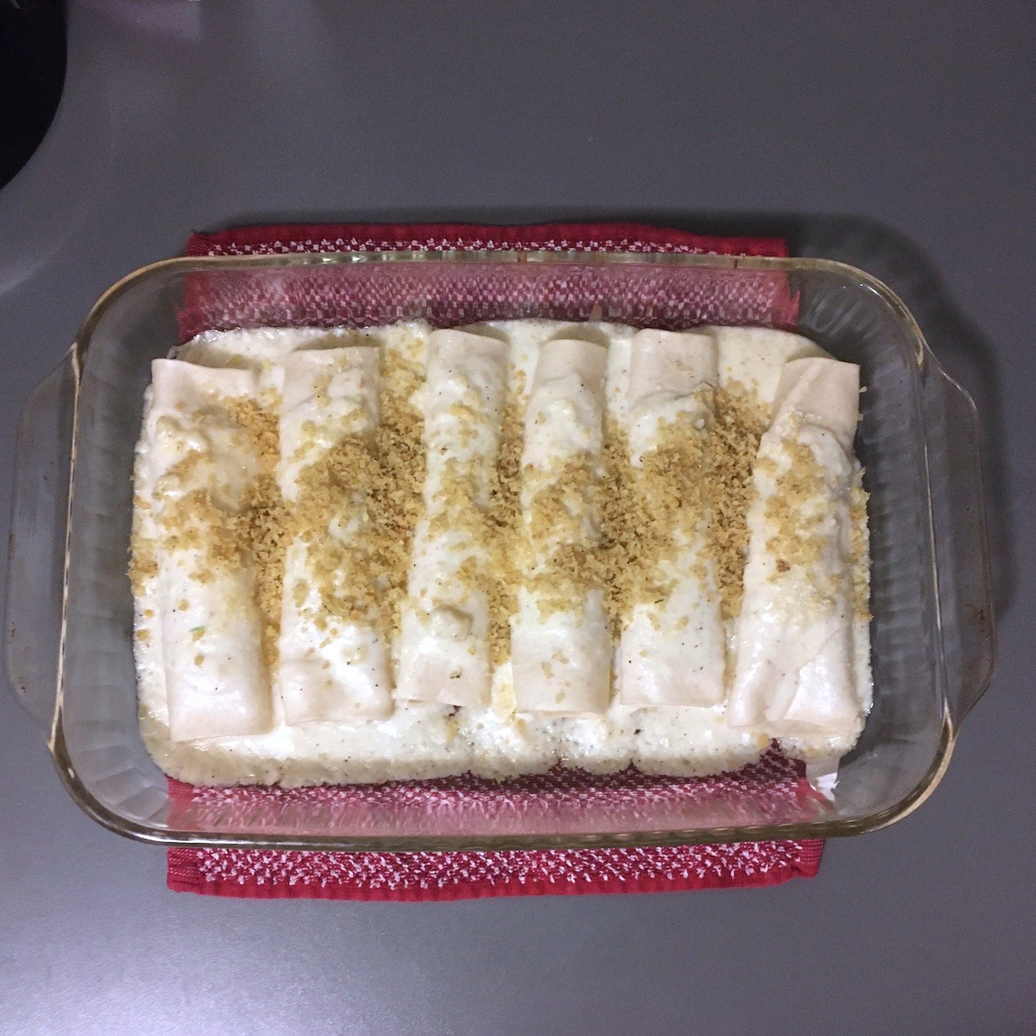 brussels sprouts canneloni topped with breadcrumbs in baking dish