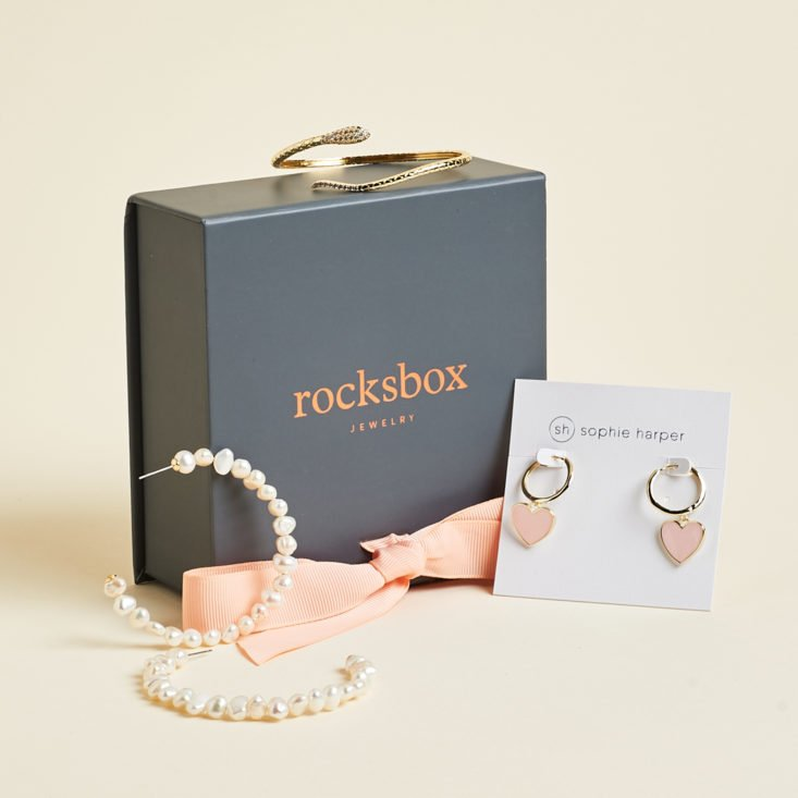 Rocksbox with designer jewelry like snake bracelet, pearl earrings, and heart hoop earrings.