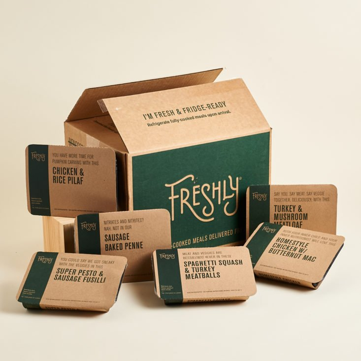 A collection of pre-packaged Freshly meals surrounding a cardboard box from Freshly.