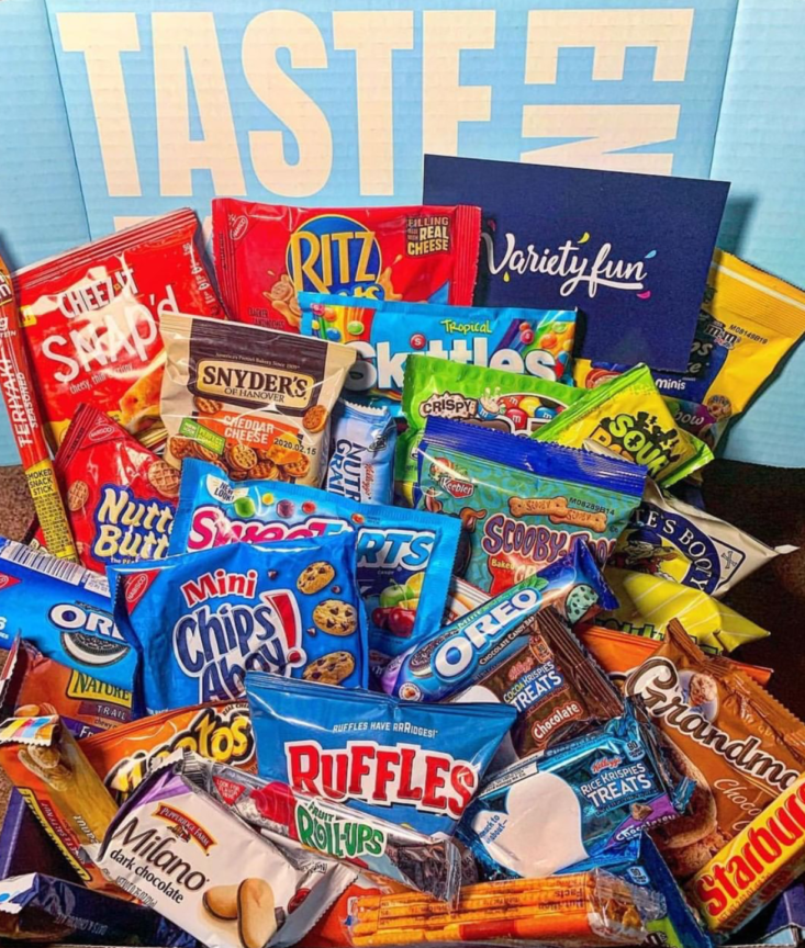 A variety of cookies, chips, candy, and more inside of a blue box.