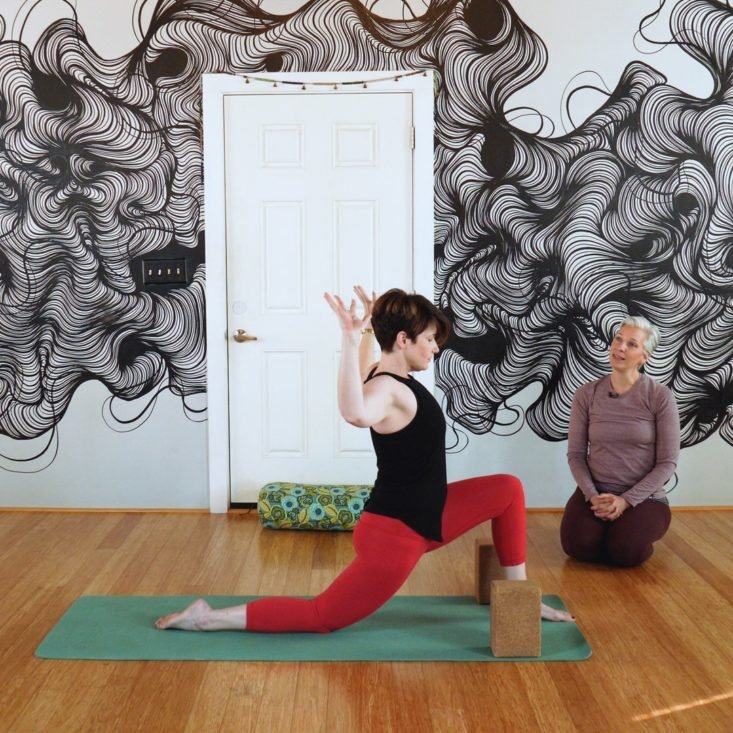 Yoga teacher guiding student.