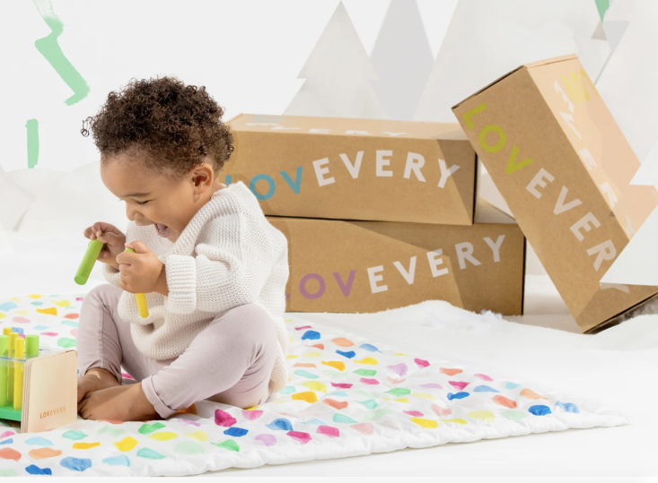 baby playing on mat with development toys