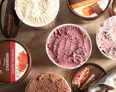 top view of ice cream cartons with lids off different flavors