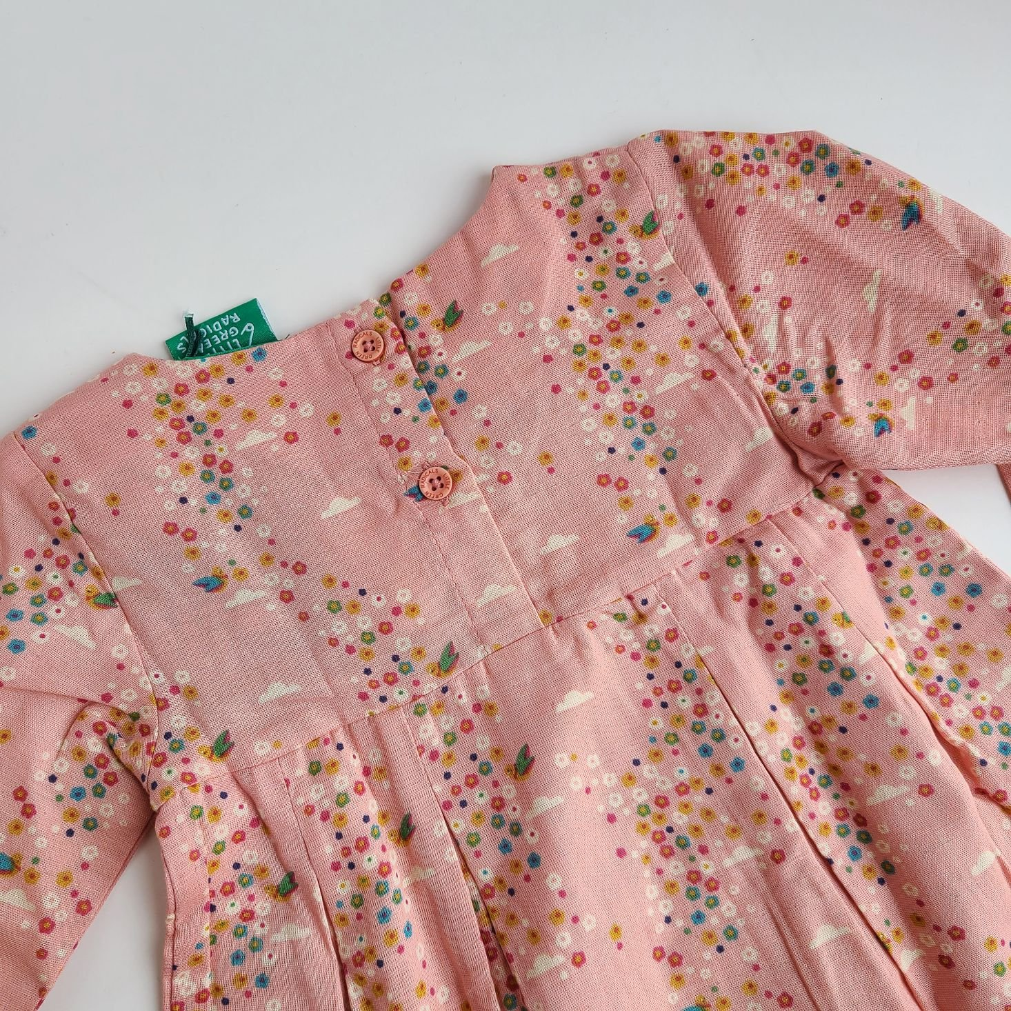 close up of the front of a Pink floral smock dress from Little Green Radicals