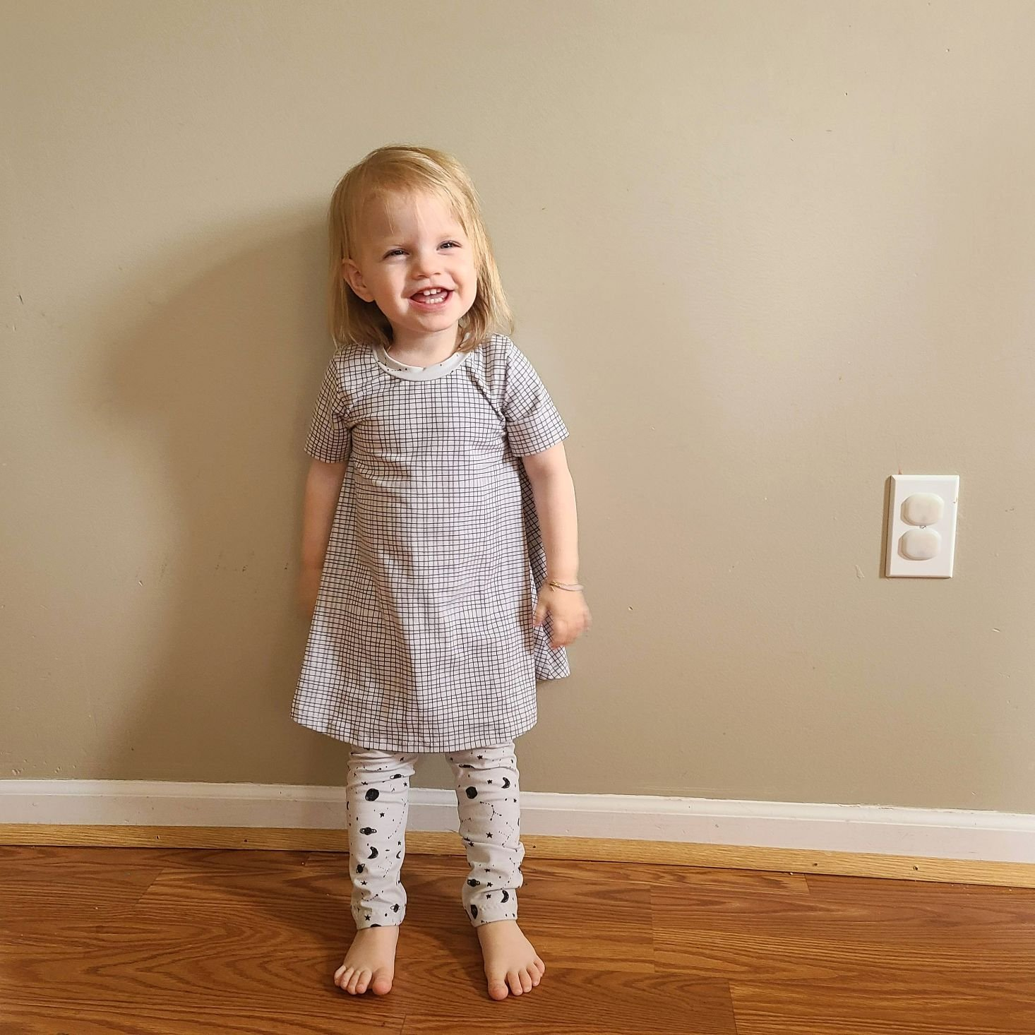 Suprisly May 2021 tee dress and space print leggings modeled on toddler girl