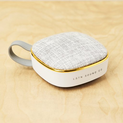 portable speaker with grey top and white bottom, plus a grey strap