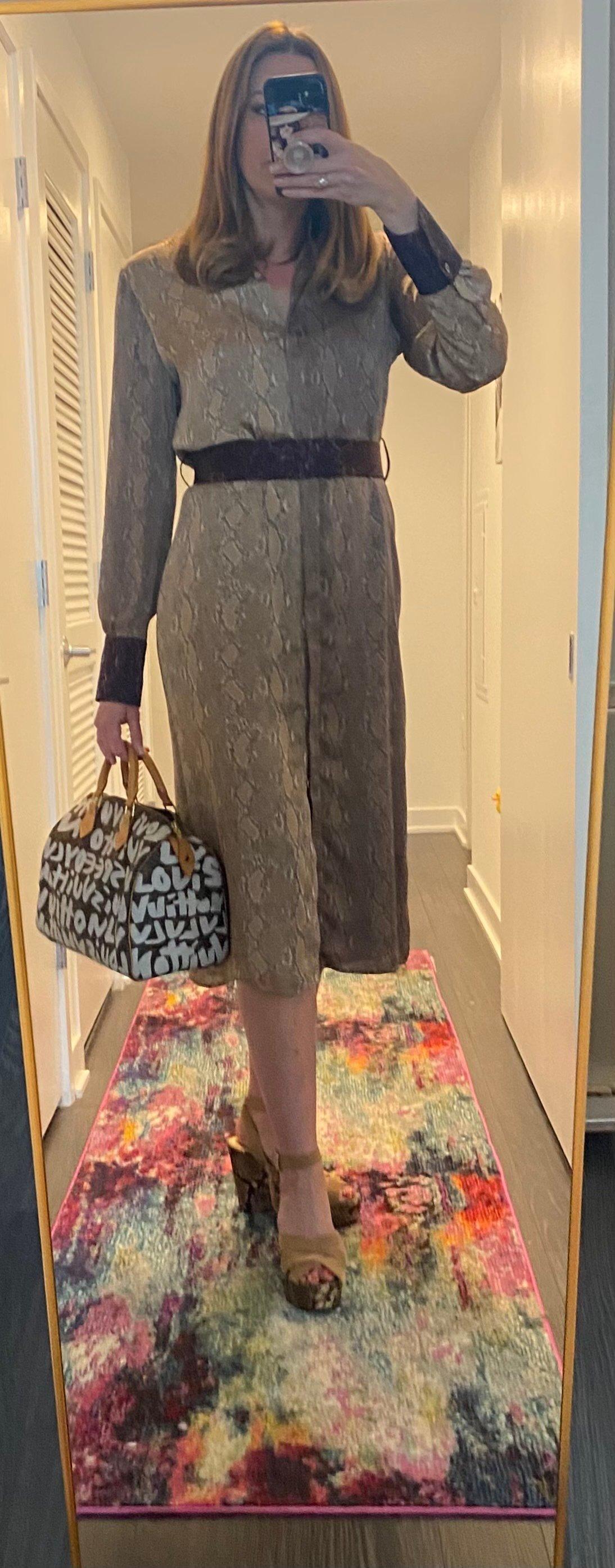 Woman in snake print dress and heels carrying handbag