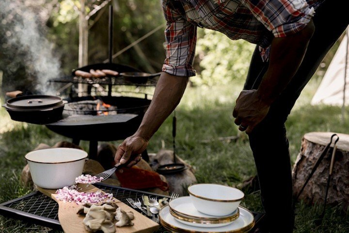 man making food on a campfire